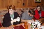 Previous: Pat Lawrence with coffee cup, Shawn Crosby working on a drawing, Colleen Crosby in red jacket.