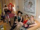 Previous: Gina Palmer in red wig at left; Karen Yearout in the black hat on the couch, next to Crystal Carroll in red, and someone else at the end of the couch. Standing behind Gina, in the background left: someone named Dawn.