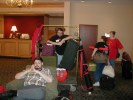 Previous: Erik V. Olson in a comfy chair, Chaz Boston Baden with a cart full of luggage, Tina Black and someone else passing by in the background.