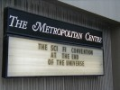 "Previous: One of the two signs at the Metropolitan Centre reads ""The Sci Fi Convention At The End Of The Universe."""